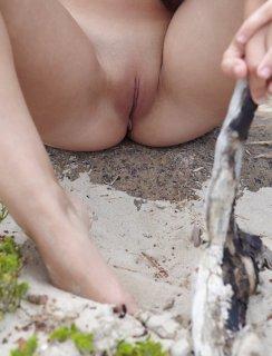 Красивая девушка сидит попкой на белом песке