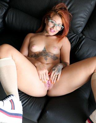 Рыжеволосая девка в очках показывает красивую попку