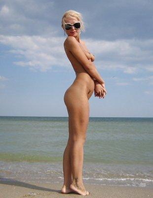 Сексуальная блондинка без трусиков загорает на пляже