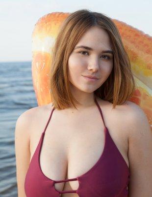 Молодая красотка позирует на пляже без купальника